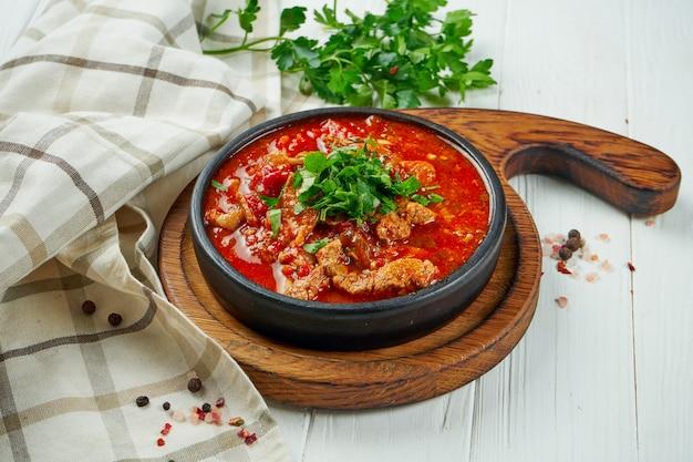 Close-up vista no saboroso, tradicional chashushuli - prato de carne aromática e picante (carne de bovino) cozida em tomates em prato de cerâmica marrom no fundo branco de madeira
