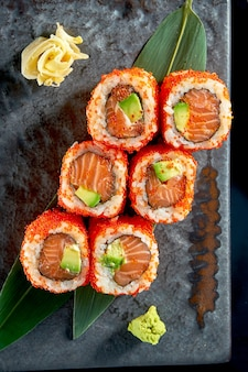 Close-up vista no saboroso uramaki com salmão, abacate e caviar tobiko. cozinha tradicional japonesa. entrega de alimentos. isolado no preto