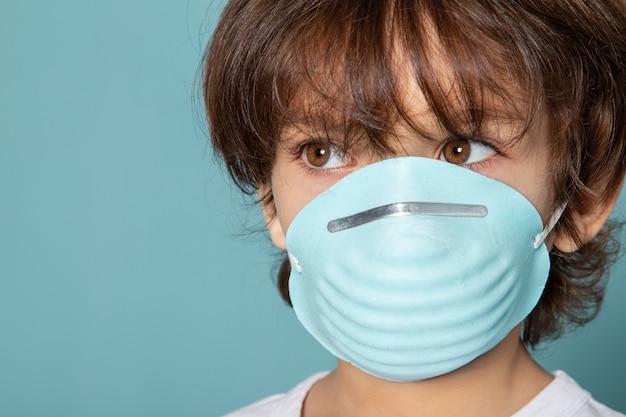 Close-up, vista pequeno garoto adorável em azul estéril máscara respiratória protetora em azul