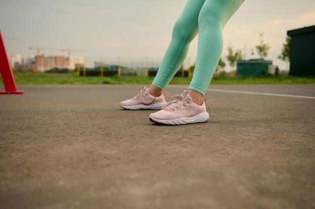 Close-up, vista recortada das pernas femininas em roupas esportivas e calçados esportivos durante o treino ao ar livre no campo de esportes. perda de peso, estilo de vida ativo, fitness, esporte e conceito de cuidados com o corpo