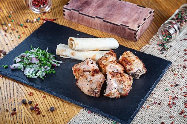 Close-up vista servido servido na grelha grill turquia. shashlik ou carne de churrasco com pita. shish kebab, comida tradicional da cozinha georgiana. copie o espaço para o design