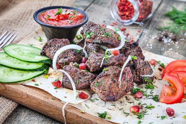 Close-up vista servido servido na vitela grelha. shashlik ou carne de churrasco com pita. shish kebab, comida tradicional da cozinha georgiana. copie o espaço para o design