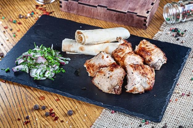 Close-up vista servido servido sobre o frango grelhado. shashlik ou carne de churrasco com pita. shish kebab, comida tradicional da cozinha georgiana. copie o espaço para o design