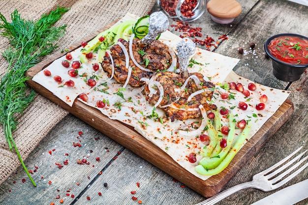 Close-up vista servido servido sobre o frango grelhado. shashlik ou carne de churrasco na pita. shish kebab, comida tradicional da cozinha georgiana. copie o espaço para o design