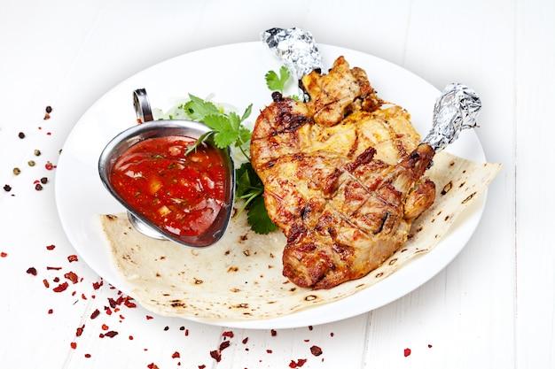 Close-up vista servido servido sobre o frango grelhado shashlik ou carne de churrasco na pita. shish kebab, comida tradicional da cozinha georgiana. copie o espaço para o design