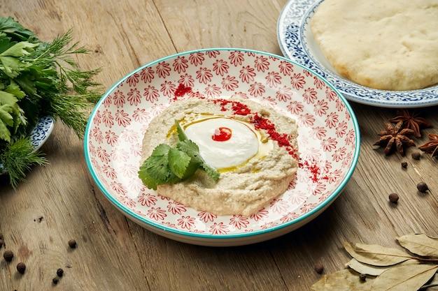 Close-up vista sobre baba ghanoush - aperitivo de levantine de purê de berinjela cozida misturada com tahine com molho de iogurte em um prato de cerâmico em uma mesa de madeira