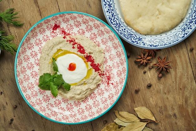 Close-up vista sobre baba ghanoush - aperitivo de levantine de purê de berinjela cozida misturada com tahine com molho de iogurte em um prato de cerâmico em uma superfície de madeira