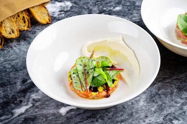 Close-up vista sobre tartare de salmão servido com pão, molho e salsa em chapa branca