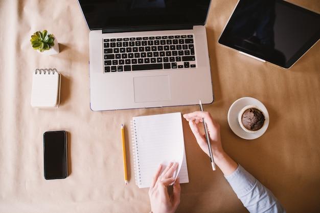 Close-up vista superior da mulher de negócios moderna vira uma nova folha de papel enquanto está sentado na mesa do escritório.