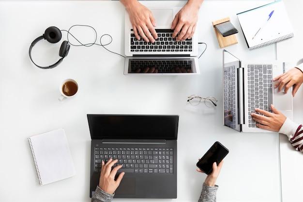 Close-up vista superior de pessoas trabalhando com laptop em uma mesa branca office concept co working