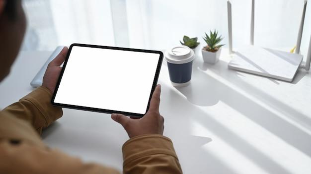 Close-up vista traseira do jovem usando tablet digital e sentado na frente do roteador de internet sem fio de alta velocidade em seu espaço de trabalho.