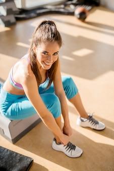 Close-up vista vertical da adorável encantadora garota feliz sorridente, olhando para a câmera enquanto amarra os cadarços no ginásio ensolarado.