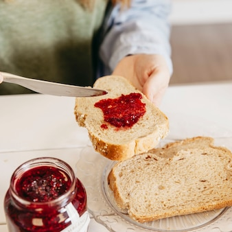Close-up woman smearing jam on bread