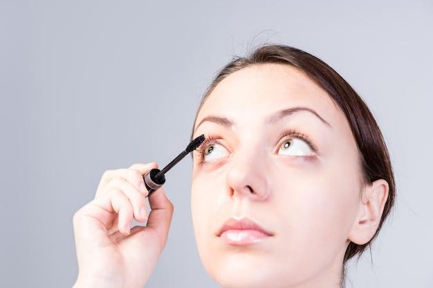 Close-up young pretty woman colocando maquiagem rímel nos cílios enquanto olha para cima, isolado em um fundo cinza.