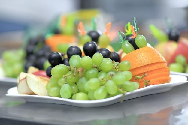 Close upplate com uvas e laranjas no fundo desfocado