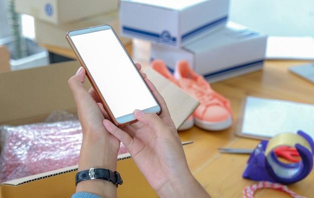 Close-ups de vendedores online usando smartphones tiram fotos dos produtos antes de serem entregues.