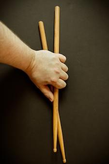 Close vertical da mão de uma pessoa segurando duas baquetas em uma superfície preta