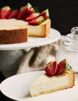 Close vertical de cheesecake de morango em um prato branco e um fundo preto