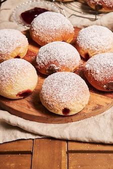 Close vertical de donuts fofinhos recheados com geleia em uma bandeja sobre a mesa sob as luzes