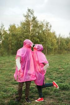 Close vertical de duas pessoas em capas de chuva de plástico rosa e fone de ouvido vr se beijando