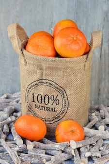 Close vertical de laranjas em um saco de estopa em galhos em frente a uma parede de madeira
