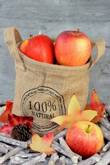 Close vertical de maçãs em um saco de estopa em galhos e folhas