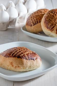 Close vertical de pães recém-assados em um prato branco sobre uma mesa de madeira
