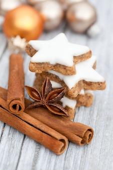 Close vertical de paus de canela e uma pilha de biscoitos de gengibre em forma de estrela em uma mesa
