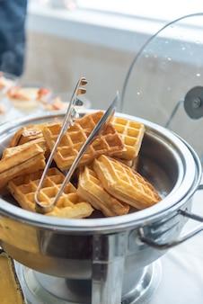 Close vertical de pequenos waffles em um fogão de metal em uma mesa de eventos