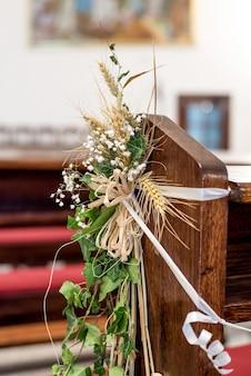 Close vertical de plantas decorativas em uma cadeira de casamento de madeira