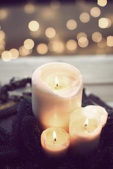 Close vertical de três velas acesas com luzes de bokeh