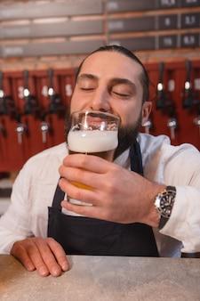 Close vertical de um barman sorrindo alegremente, sentindo o cheiro de cerveja recém-feita no copo