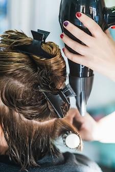 Close vertical de um cabeleireiro secando o cabelo curto de uma mulher em um salão de beleza