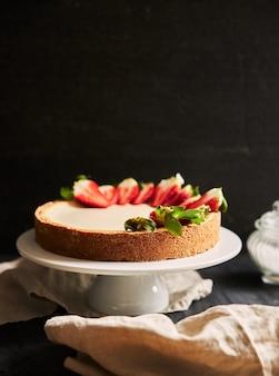 Close vertical de um cheesecake de morango em um prato branco
