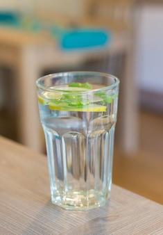 Close vertical de um copo de água com limão e hortelã com um espaço desfocado