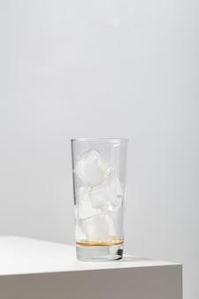 Close vertical de um copo vazio com cubos de gelo em cima da mesa sob as luzes