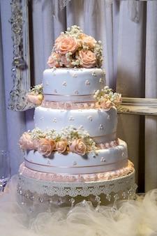Close vertical de um lindo bolo de três camadas com enfeites de rosas