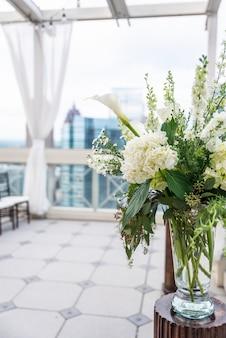 Close vertical de um lindo buquê com flores brancas em um vaso de vidro