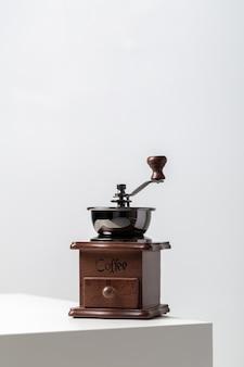 Close vertical de um mini moinho de café vintage na mesa sob as luzes