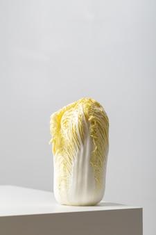 Close vertical de um repolho napa na mesa sob as luzes contra um fundo branco