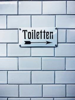 Close vertical de um sinal de banheiro com uma escrita alemã