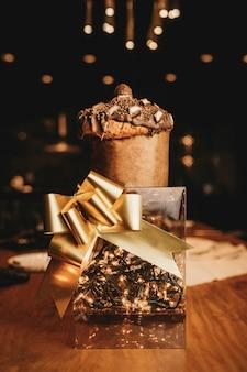 Close vertical de uma caixa romântica com luzes, uma fita dourada e um muffin