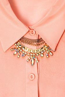 Close vertical de uma camisa de gola cor de pêssego com um lindo colar