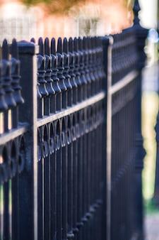 Close vertical de uma cerca de metal em uma calçada