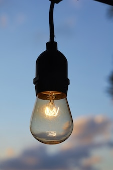 Close vertical de uma lâmpada acesa contra o céu nublado