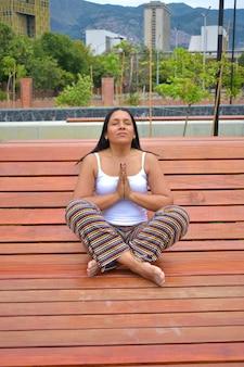 Close vertical de uma mulher latina morena meditando em um banco de um parque