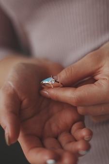 Close vertical de uma mulher segurando um lindo anel de diamante de ouro