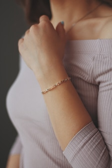 Close vertical de uma mulher usando uma pulseira de ouro