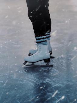 Close vertical de uma pessoa de patins brancos no gelo durante a nevasca
