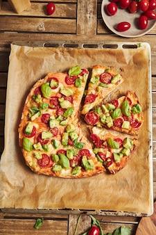 Close vertical de uma pizza com legumes na mesa de madeira